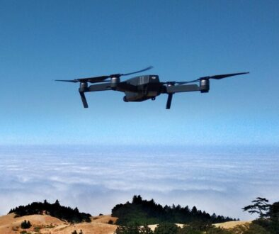 black drone on air over cloudy sky at daytime