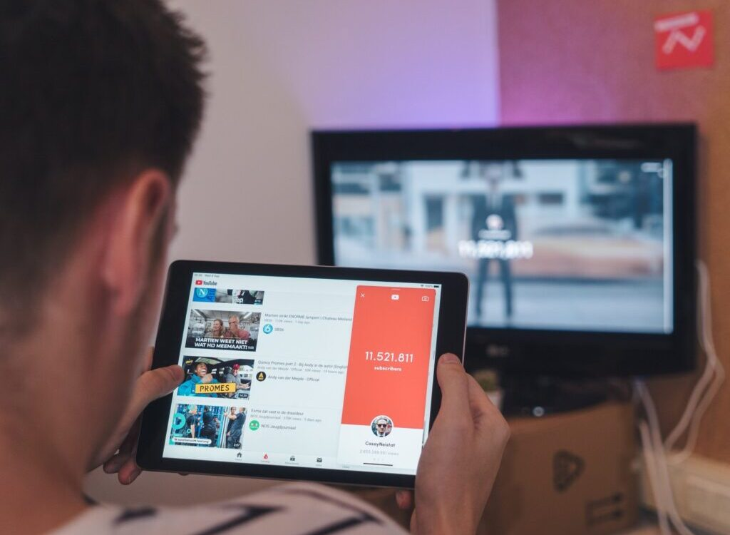 man browsing tablet sitting in front of TV