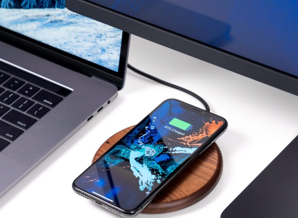 clear glass teacup on table beside phone and laptop