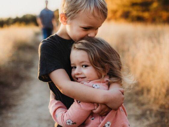 boy in black t-shirt hugging girl in red and white polka dot dress