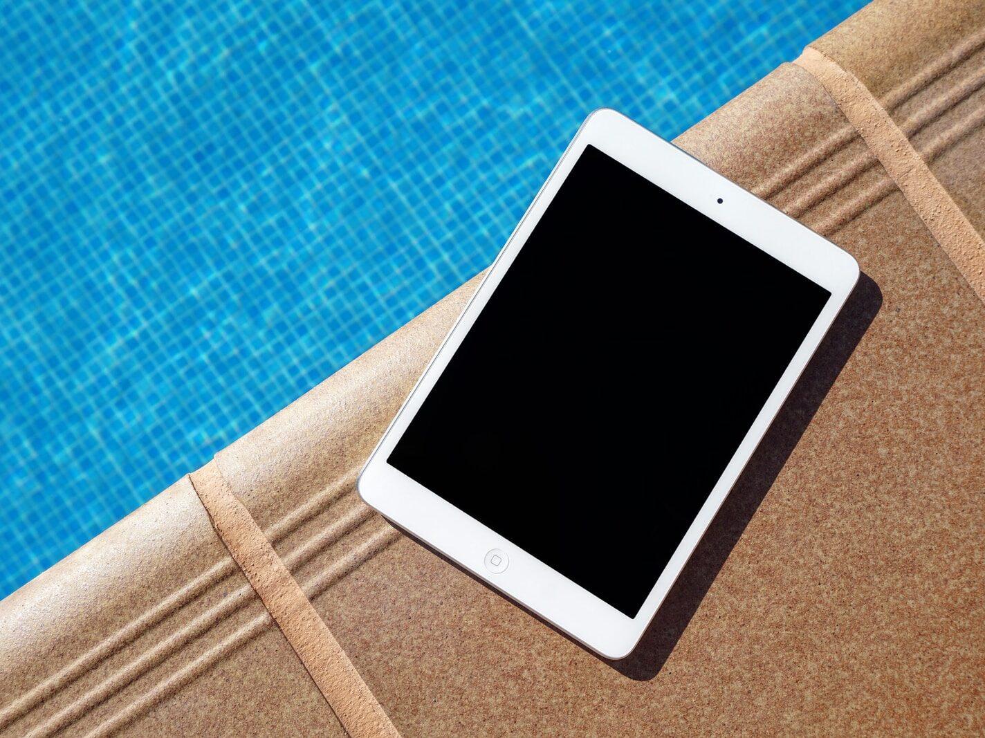 white iPad beside swimming pool