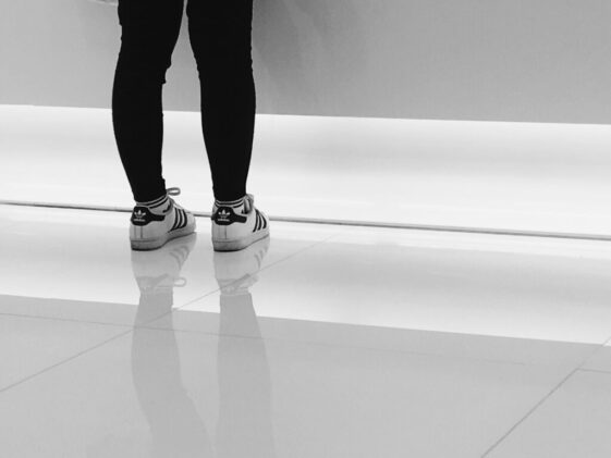 person wearing pair of white-and-black adidas running shoes